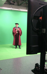 Man in maroon graduation robes and black cap stands in the distance on a green screen background.